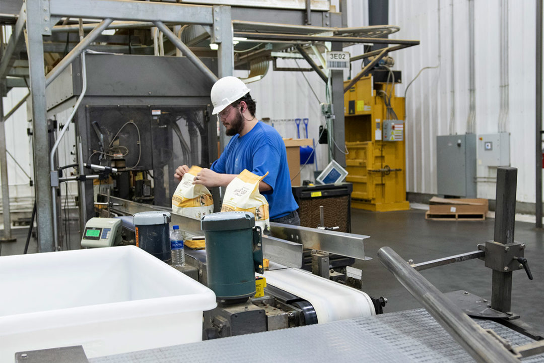 Man works packaging line at pet food co-manufacturing plant