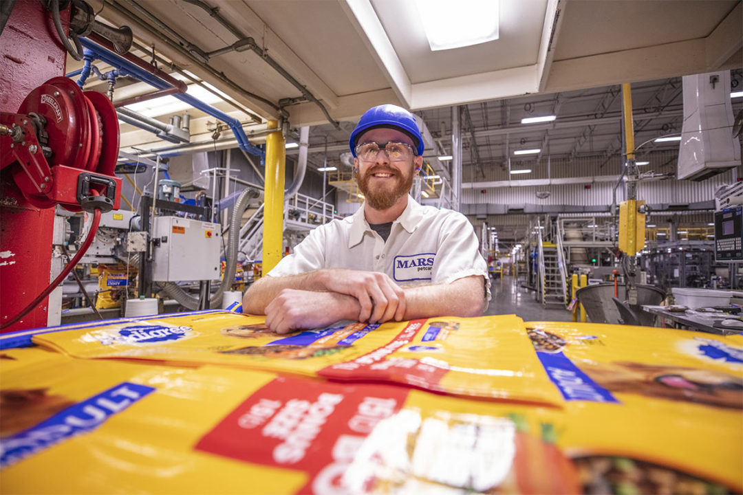 Employee smiling by PEDIGREE packaging at Mars Petcare's Mattoon, Illinois facility