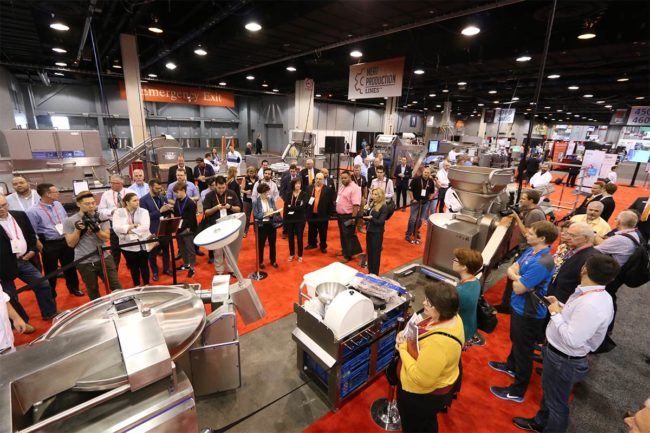 Crowd gathered around production line exhibit at PROCESS EXPO