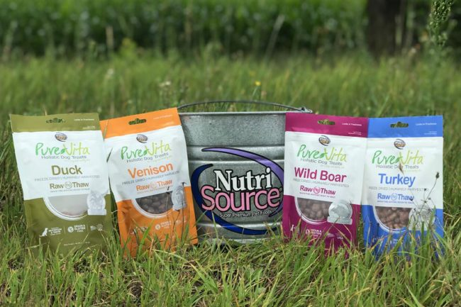 NutriSource bucket on grass surrounded by PureVita dog treats