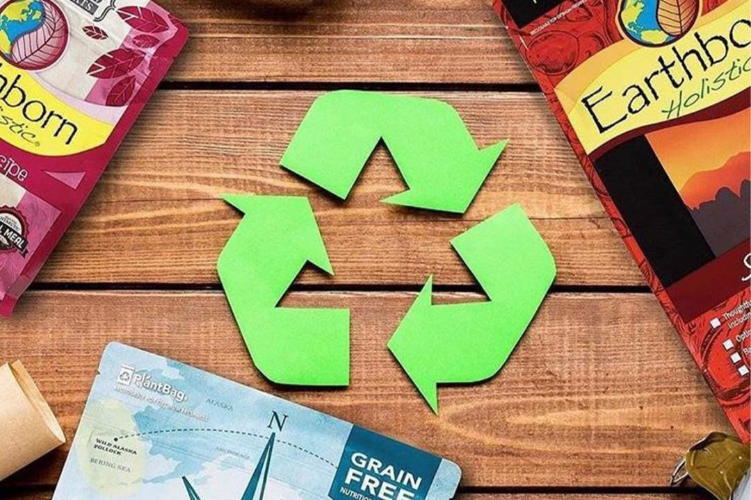 Green recycle sign on wooden table with Earthborn Holistic packaging around edges