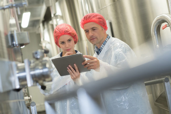 Two employees in red hair nets discussing over clipboard (©STOCKR - STOCK.ADOBE.COM)