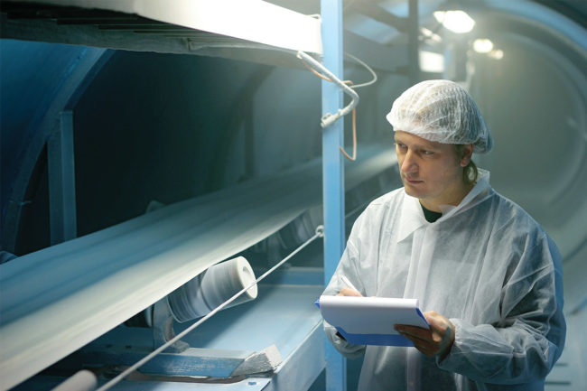 Man in white clean suit evaluating industrial processing machinery (©STOCKR - STOCK.ADOBE.COM)