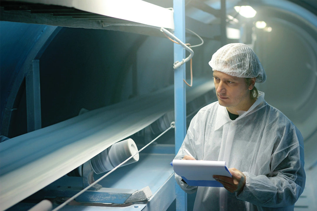 Man in white clean suit evaluating industrial processing machinery