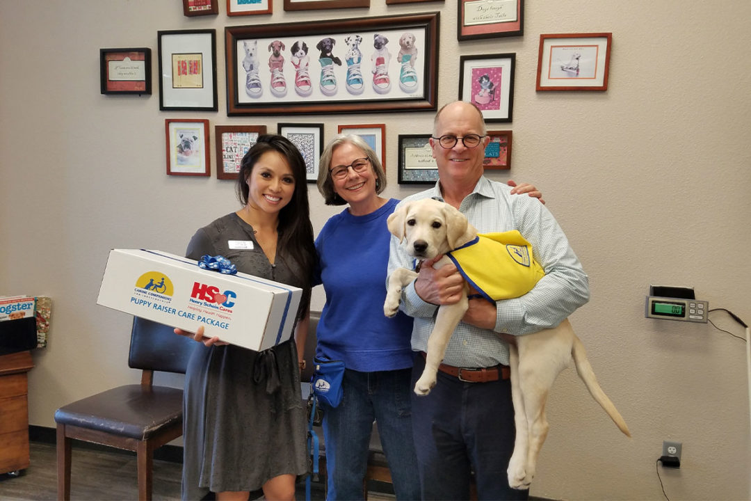 Covetrus representative Uyen Ta (left) presents 2,000th Covetrus Puppy Care Package to Canine Companions volunteer puppy raiser Kim Brewer (middle), Dr. Lee Kaplow (right) of Lakeside Pet Hospital and Fig, a future Canine Companions assistance dog.