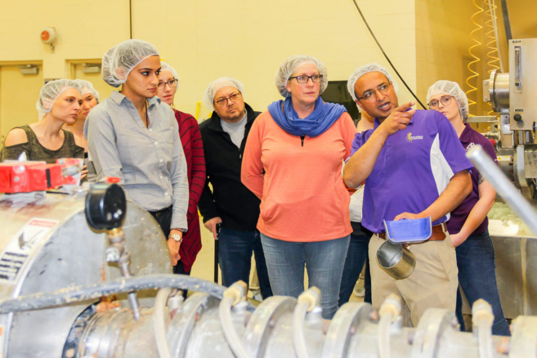 Participants from the IGP-KSU Pet Food Formulation for Commercial Production course visiting the O.H. Kruse Feed Mill with Sajid Alavi, professor within Kansas State's Grain Science and Industry, to discuss the extrusion process.