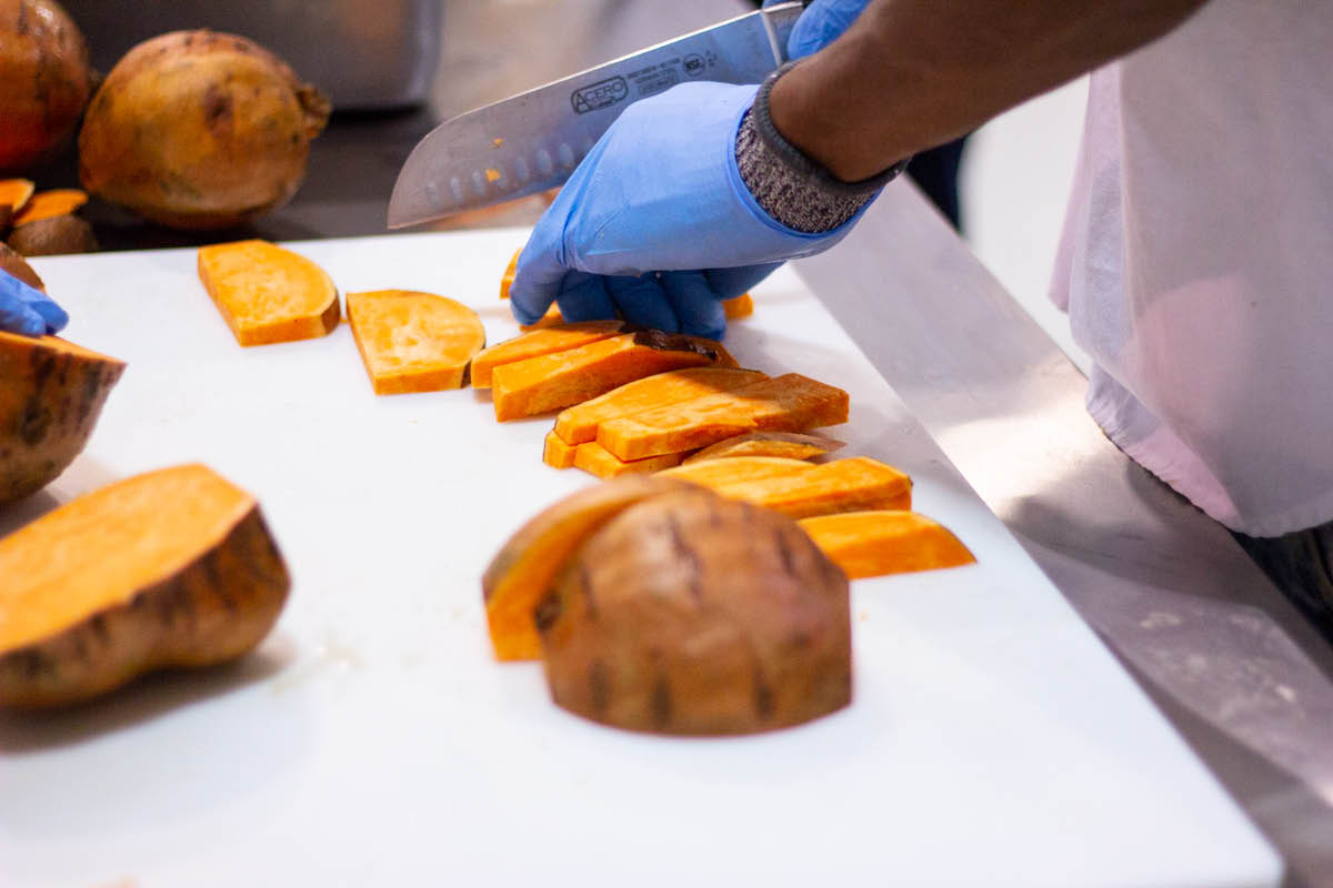 NomNomNow employee cuts sweet potatoes for fresh pet food production