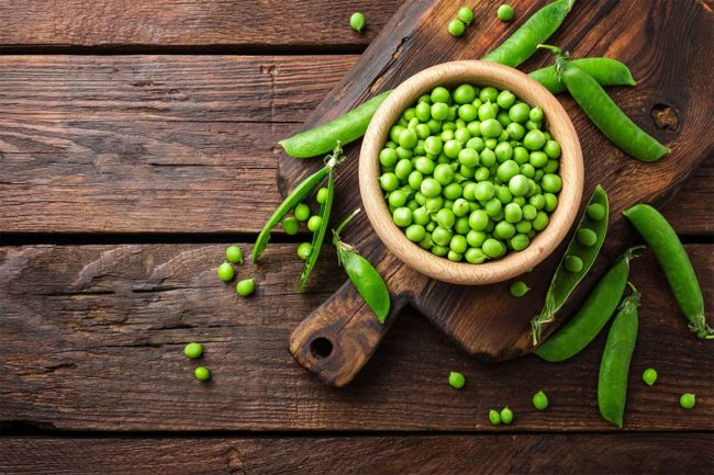 Bowl of peas on wooden table (©STOCKR - STOCK.ADOBE.COM)