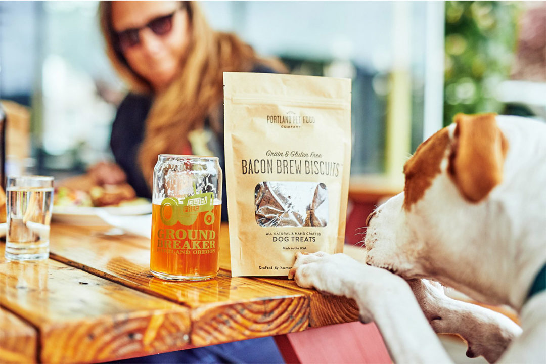 Portland Pet Food Bacon Brew Biscuits on table next to beer